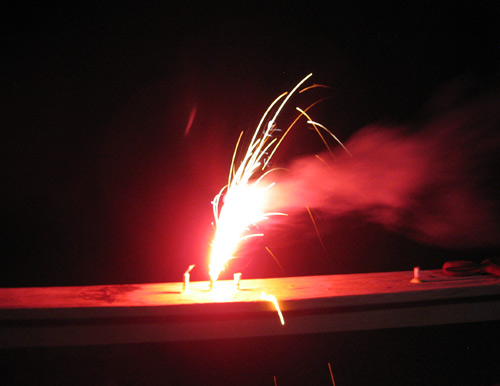 A little red firework sending up a foot-high jet of flame on a porch railing