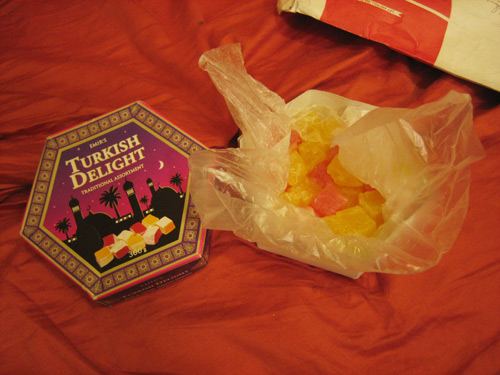An open hexagonal box of Turkish Delight lying on orange cloth, with the corner of a long-distance envelope in the corner