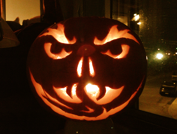 An evil-looking jack-o-lantern sitting in front of a window. Big hairy brows, fangs, a forked tongue and a wicked grin. You can see a night time street with cars parked outside.