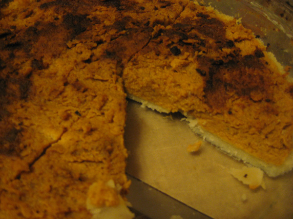 A pumpkin pie with the blackened top scraped off, revealing chunky insides and a raw bottom crust