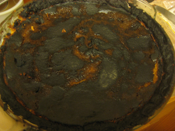 A pumpkin pie burned black and crusty on top